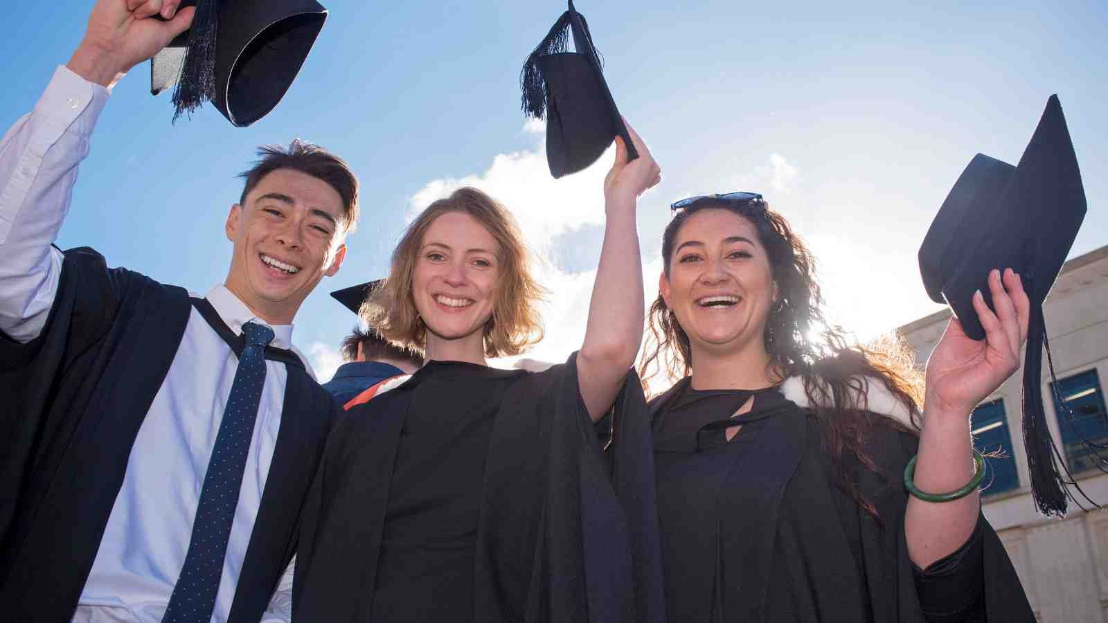 Three students raising their graduation hats in celebration at the May graduation ceremonies